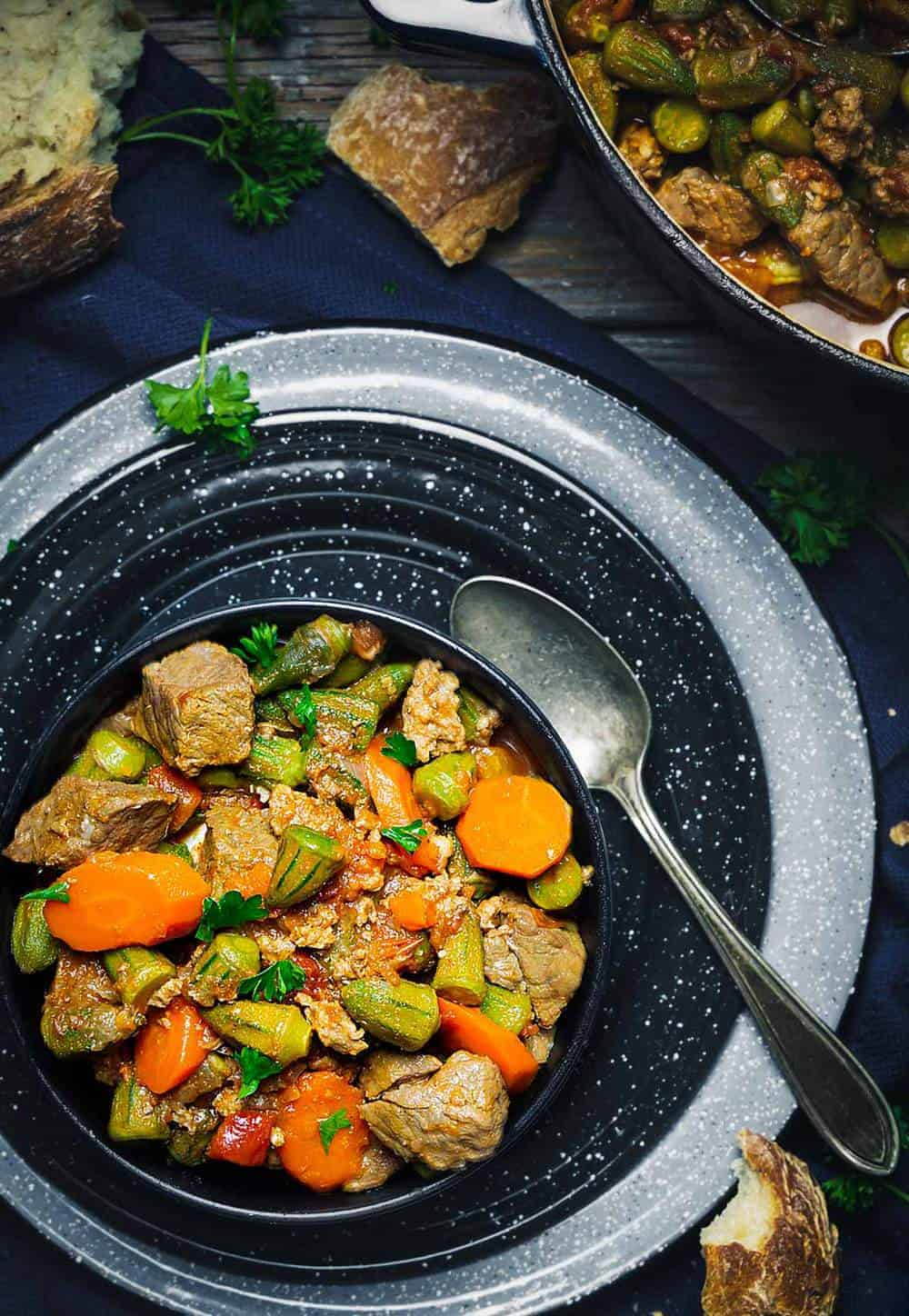 Plated bowl of okra stew with meat and vegetables on two larger plates with a spoon.