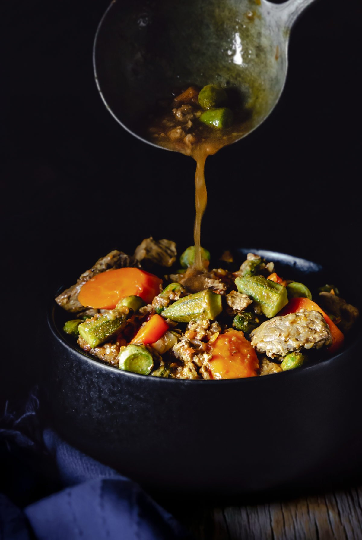 A ladle pouring the okra stew over a black bowl with meat and vegetables.
