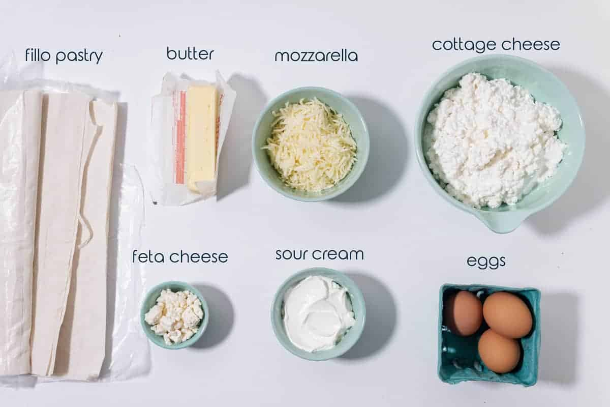 Ingredients for cheese pie with fillo dough, eggs, and three types of cheese on the counter.