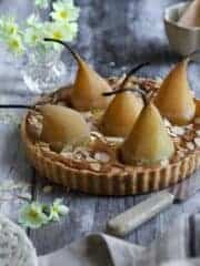 A French almond tart with whole poached pears sitting on a gray background.