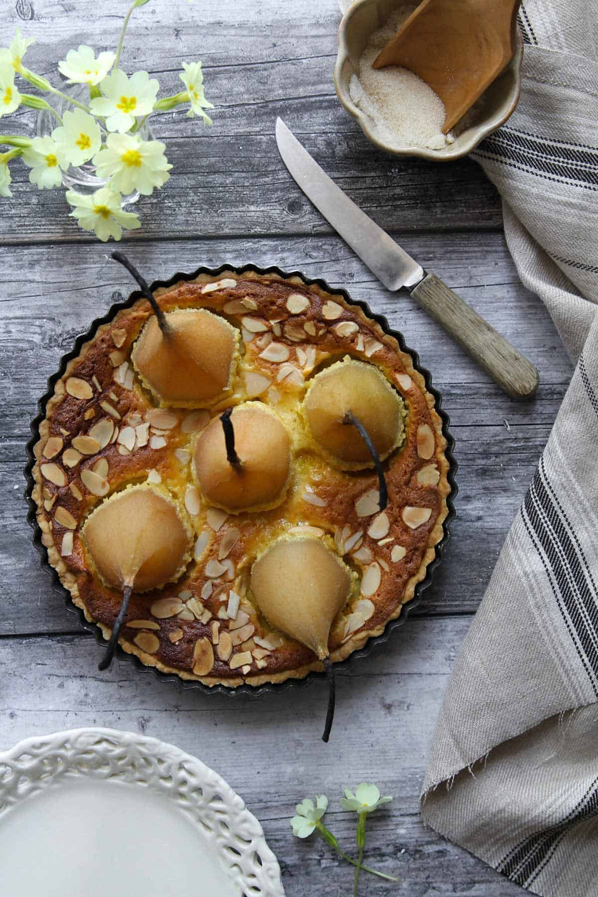 An overhead view of the round cake with five whole pears standing up in it.