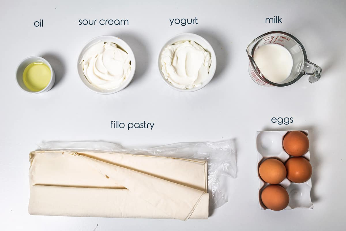 Ingredients for the egg pie with fillo eggs, sour cream, and yogurt on the counter.