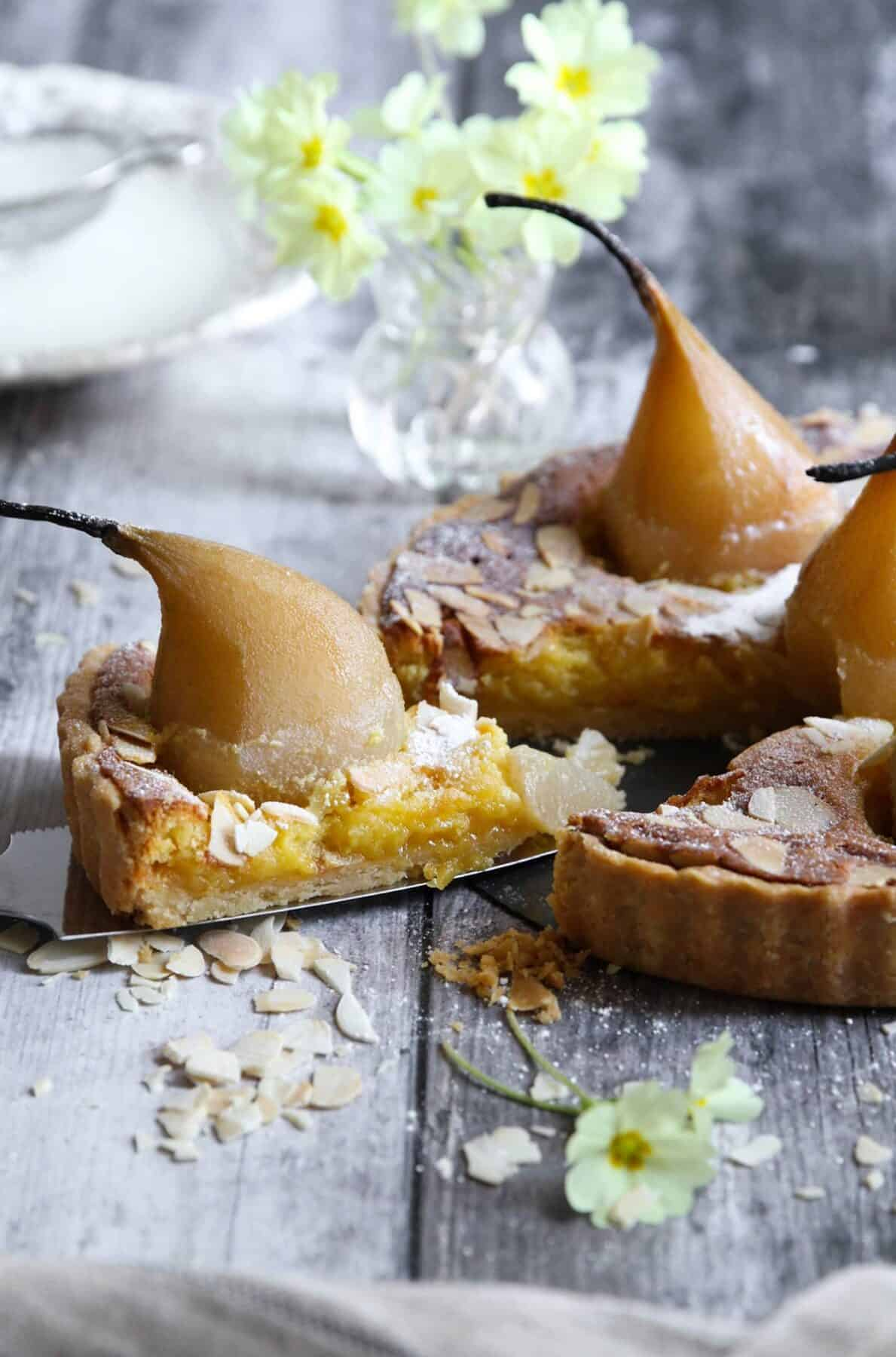 A slice with a whole pear cut out of the tarte bourdaloue.