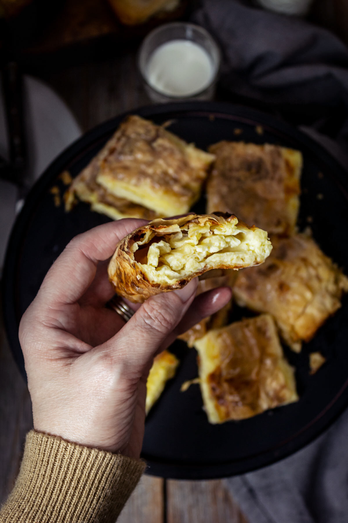 A person holding a piece of fillo cheese pie in a hand showing the filling inside.