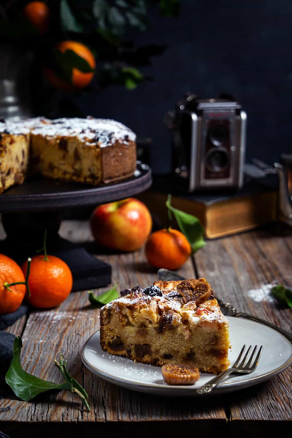 A slice of Italian apple fig polenta cake on a plate with the whole cake and citrus fruit in the background.