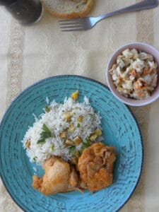 Greek-style chicken stew with rice on a blue plate.