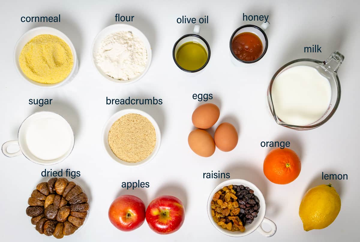 Ingredients for the cornmeal cake including eggs, sugar, apples, citrus, and dried fruit.