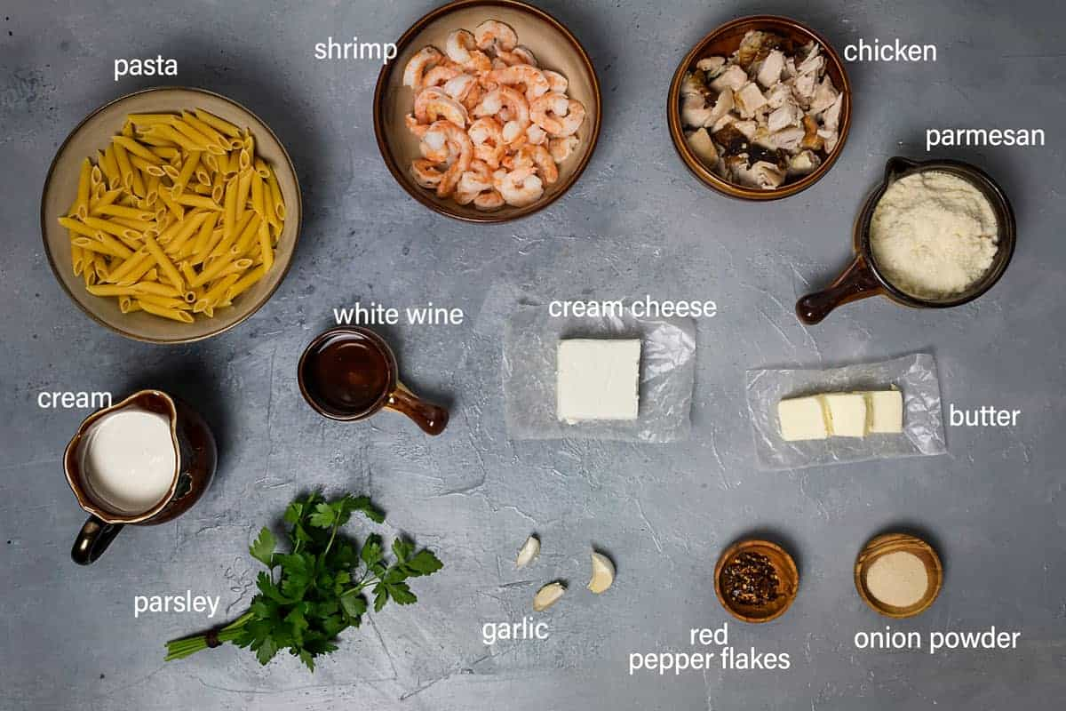 Ingredients for the pasta alfredo on the table with cream cheese, garlic, cooked chicken, and shrimp.