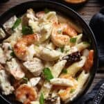 A close up of creamy penne Alfredo with chicken and shrimp in a bowl.