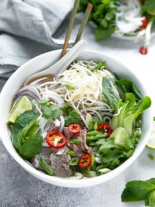 A bowl of pho with vegetables, beef, and noodles.