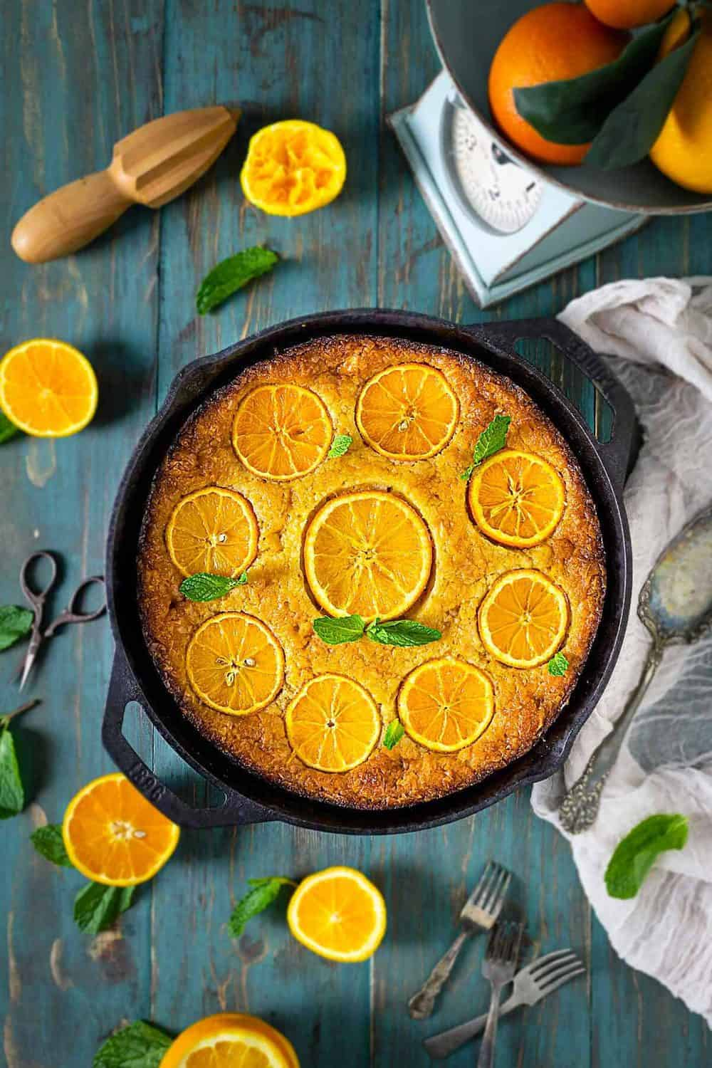 Overhead photo of a skillet with fillo and orange cake on a table with orange halves.