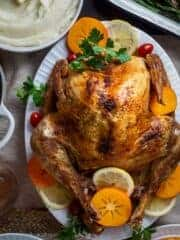 A whole roasted turkey on a platter with lemon slices.
