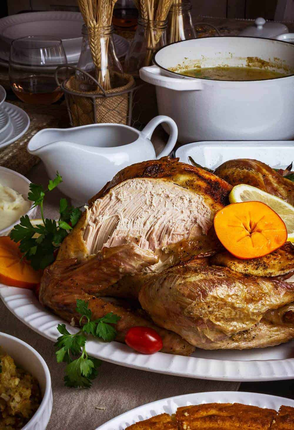 Side shot of turkey roast with a portion of the breast cut off and surrounded by side dishes.