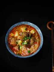 A bowl of ramen soup with beef on a black background.