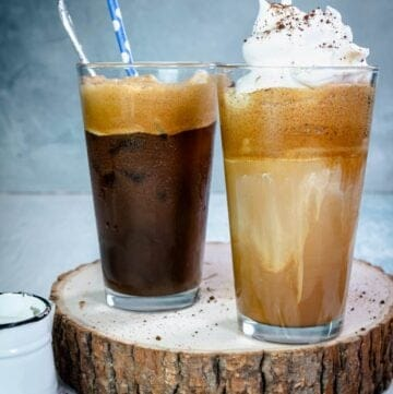 Two glasses with Greek frappe, one with whipped cream and straws on a wooden plank.