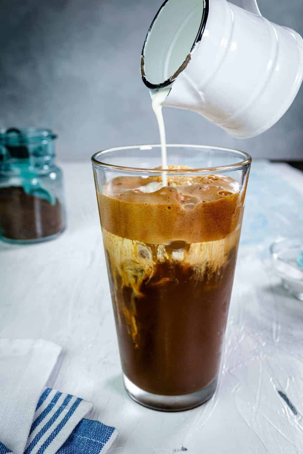 Pouring milk over a glass with Greek frappe.