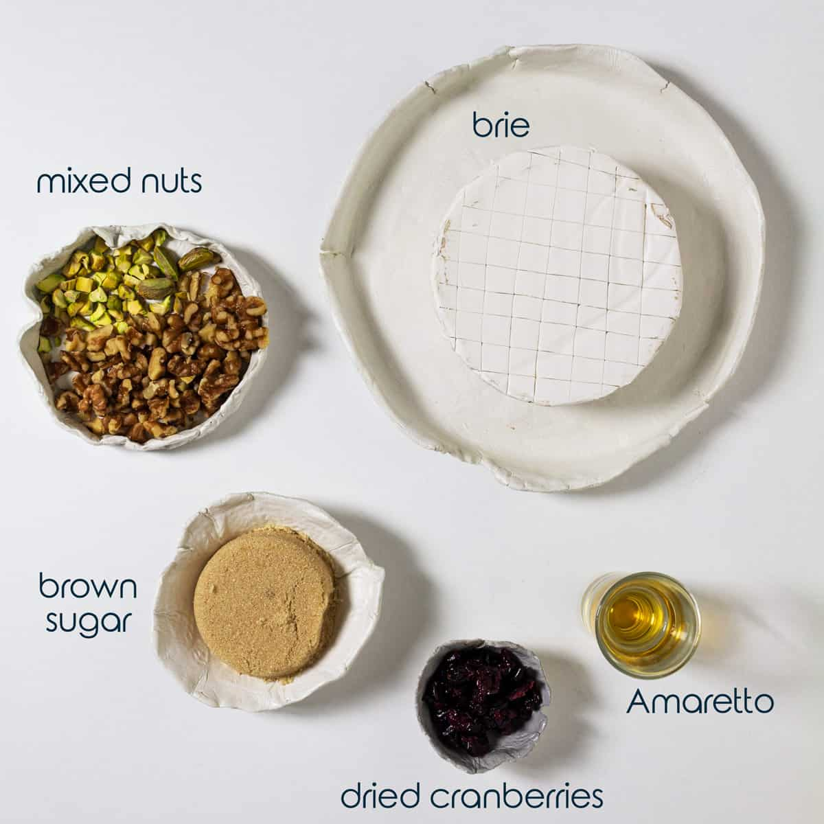 Ingredients for baked brie recipe with sugar, nuts, and dried fruit.