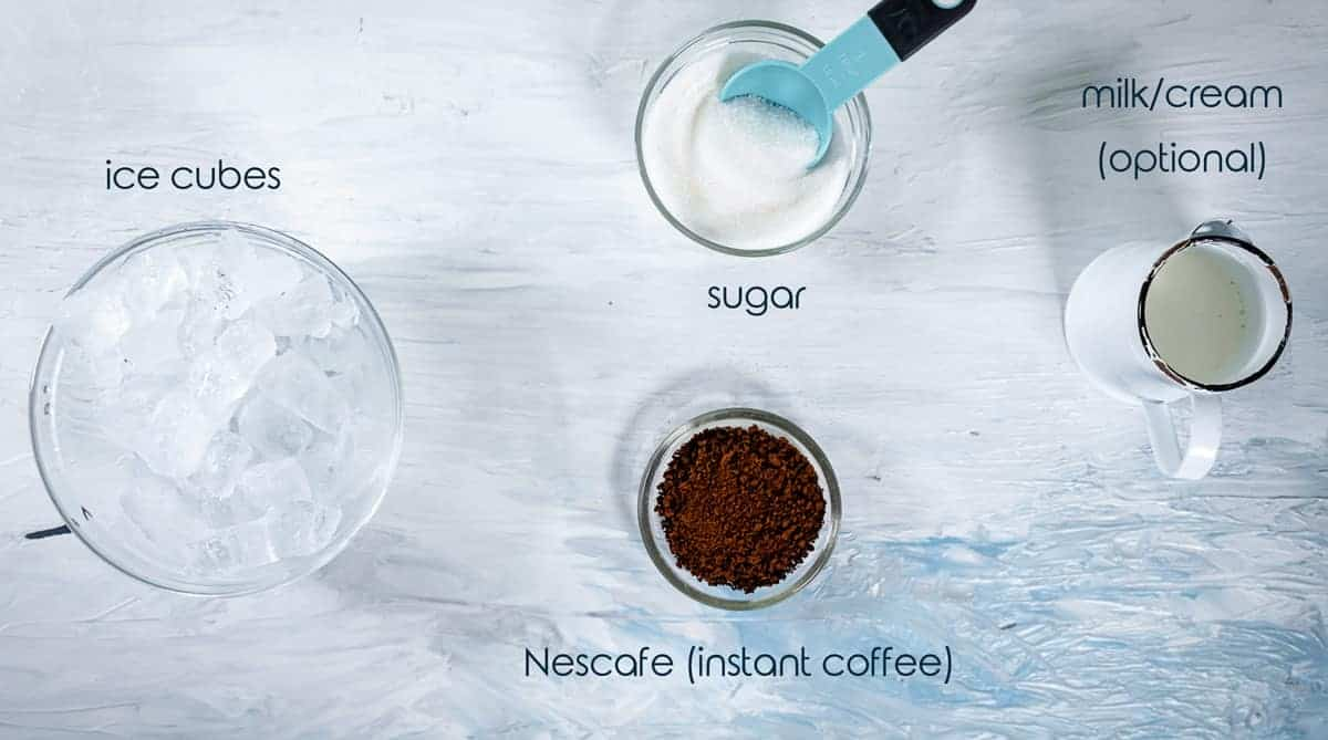 Ingredients for the Greek ice coffee drink on a counter with instant coffee, sugar, and ice.