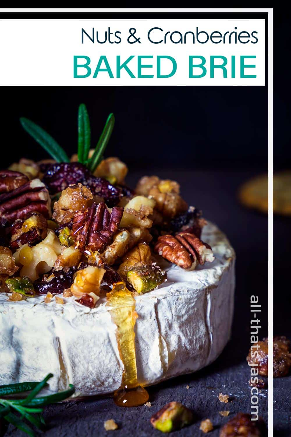 A close up of roasted brie with nut topping and text overlay.