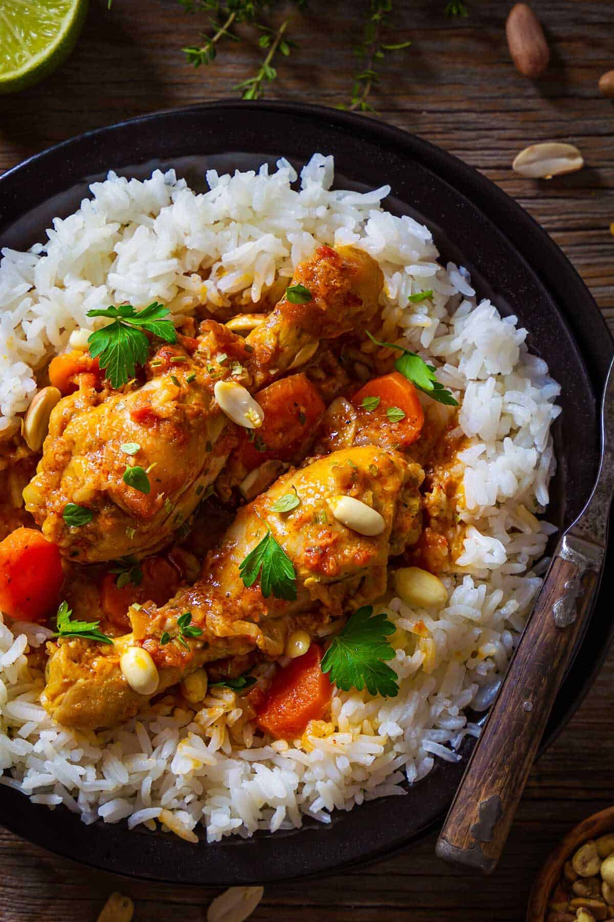 A close up shot of Djerma stew with chicken and peanuts over rice.