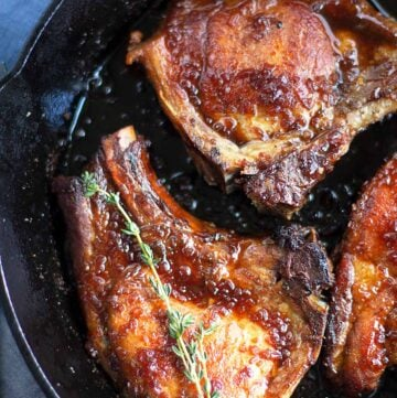 Close up of browned pork chops in a skillet with thyme twig.
