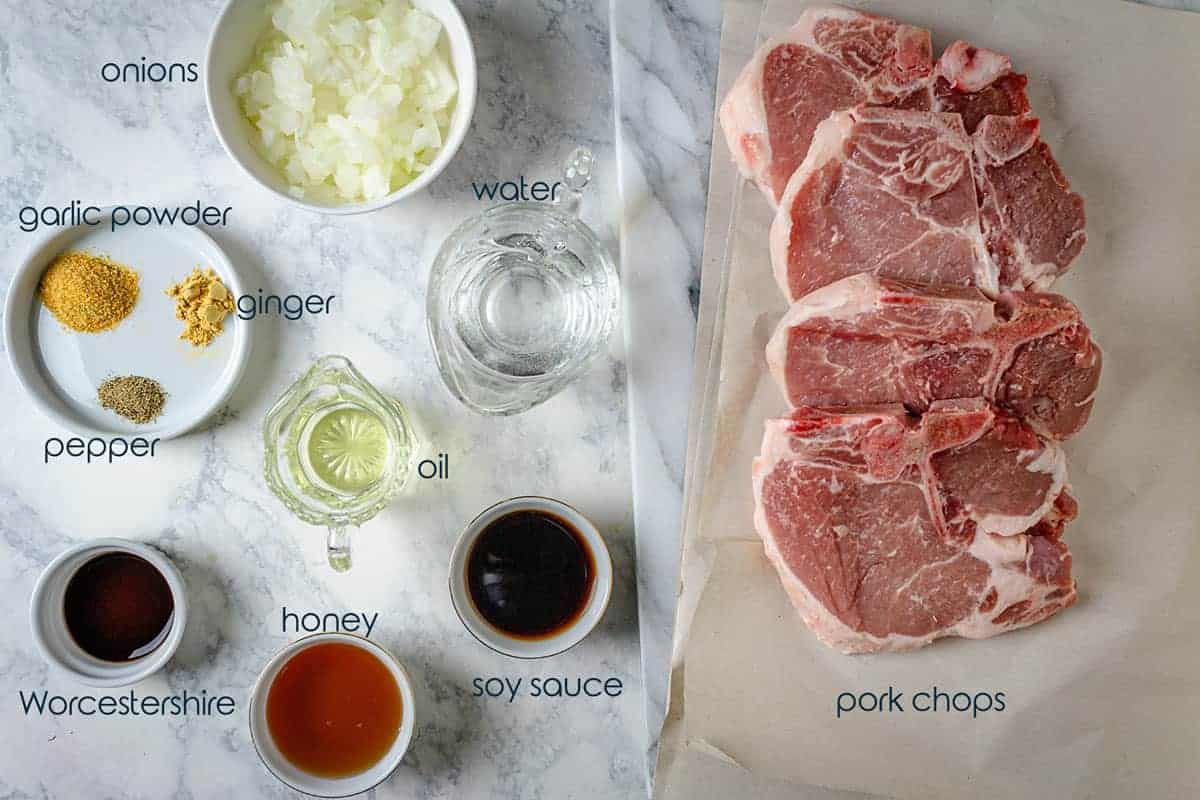 Ingredients for pork chops with honey glaze including the meat, spices, and onions.
