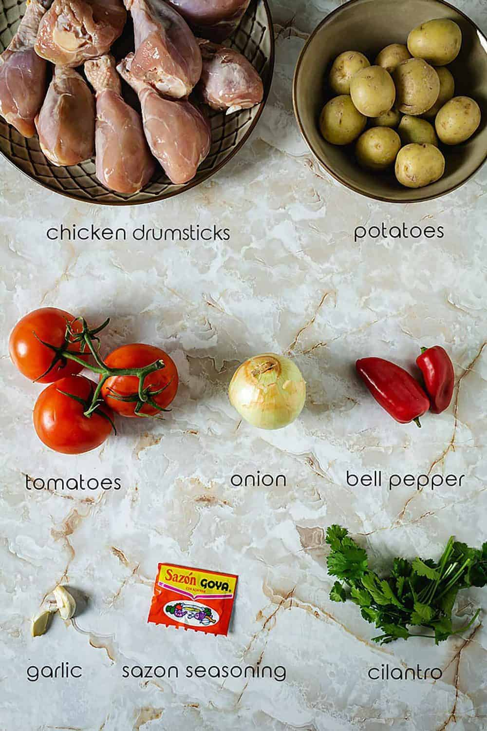 Ingredients for Sudado de Pollo with chicken drumsticks, potatoes, tomatoes, and seasonings.