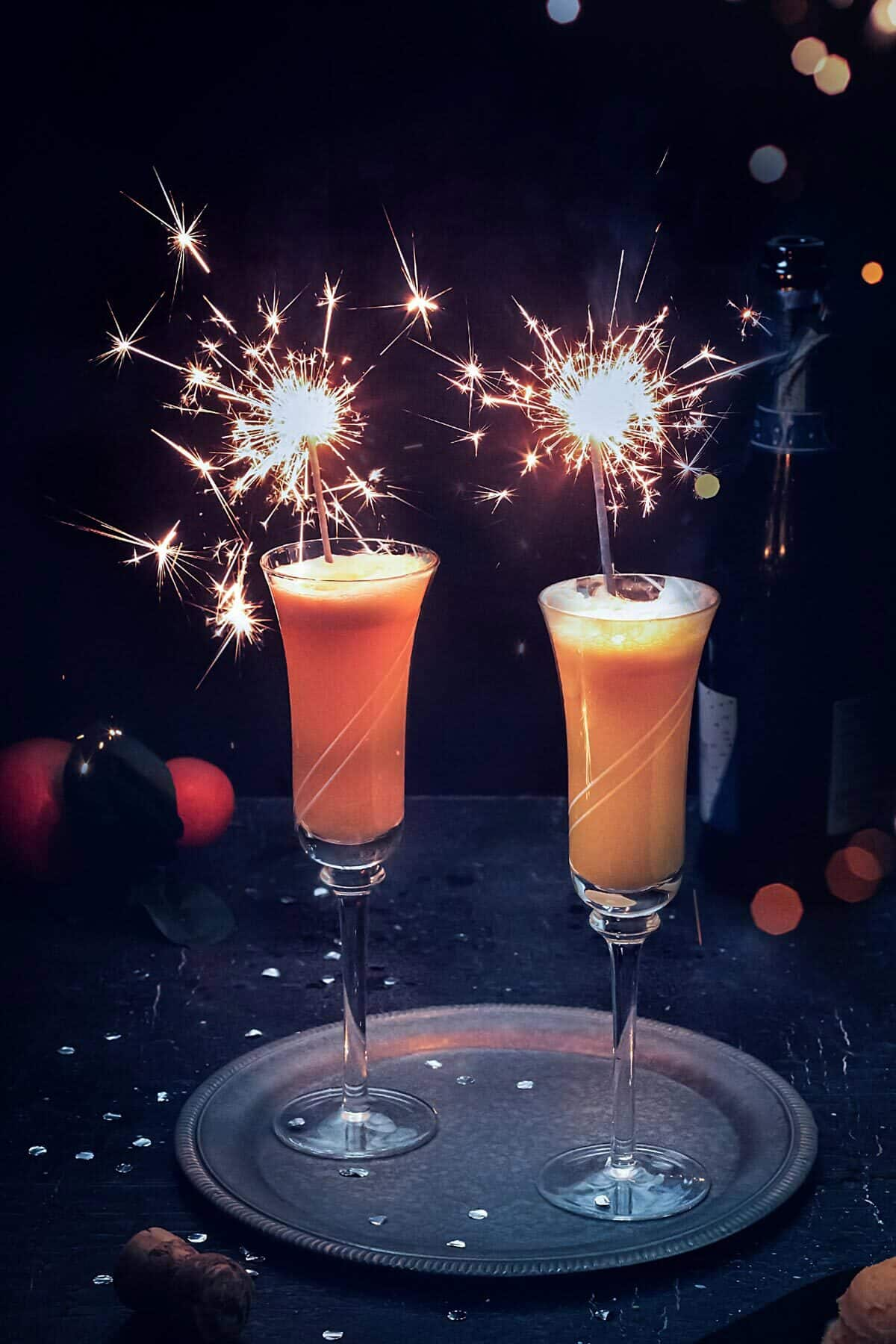 Two champagne flutes with mimosa cocktail and sparkles.
