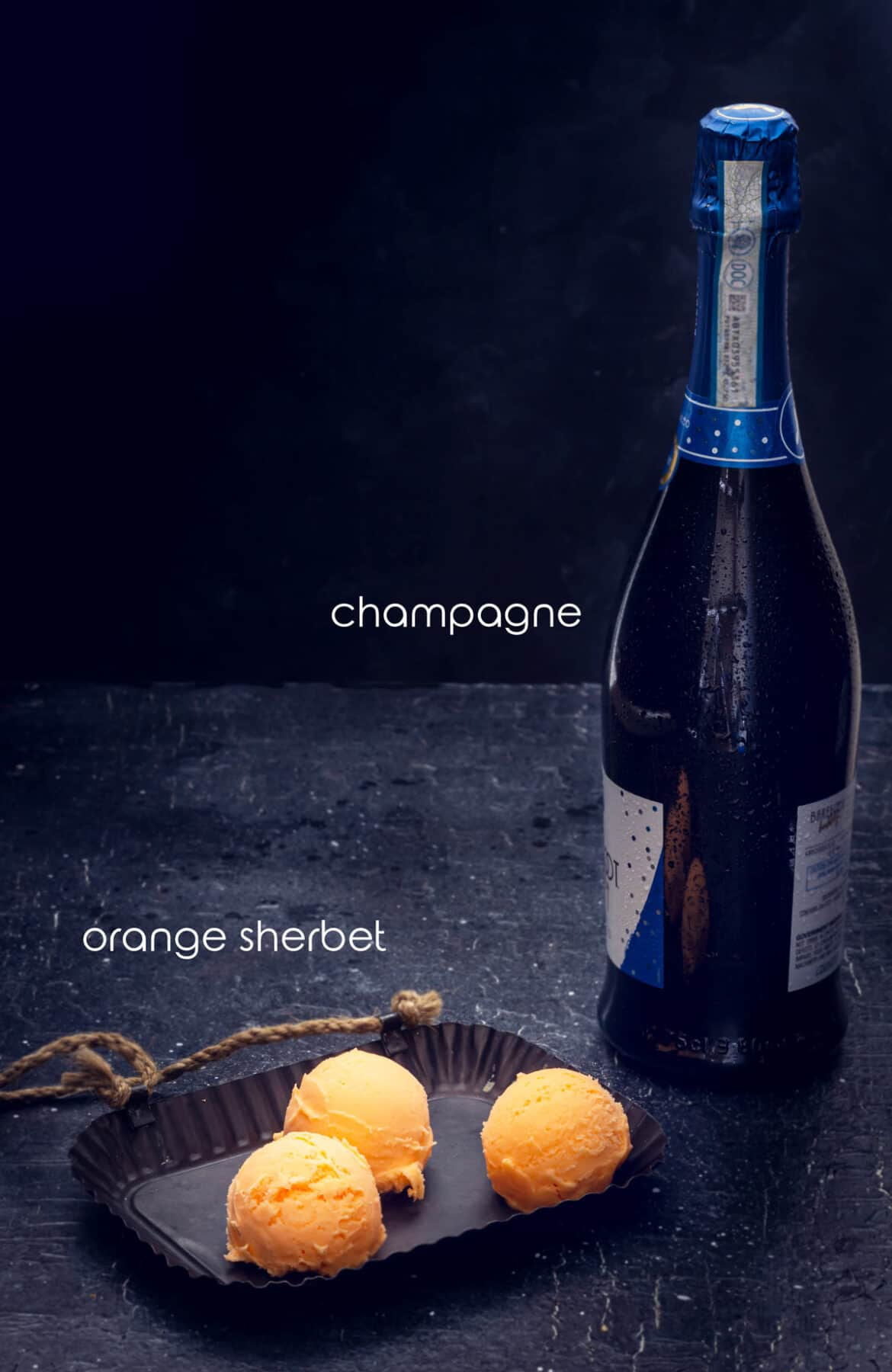 Ingredients for mimosa cocktail including champagne and orange sherbet.
