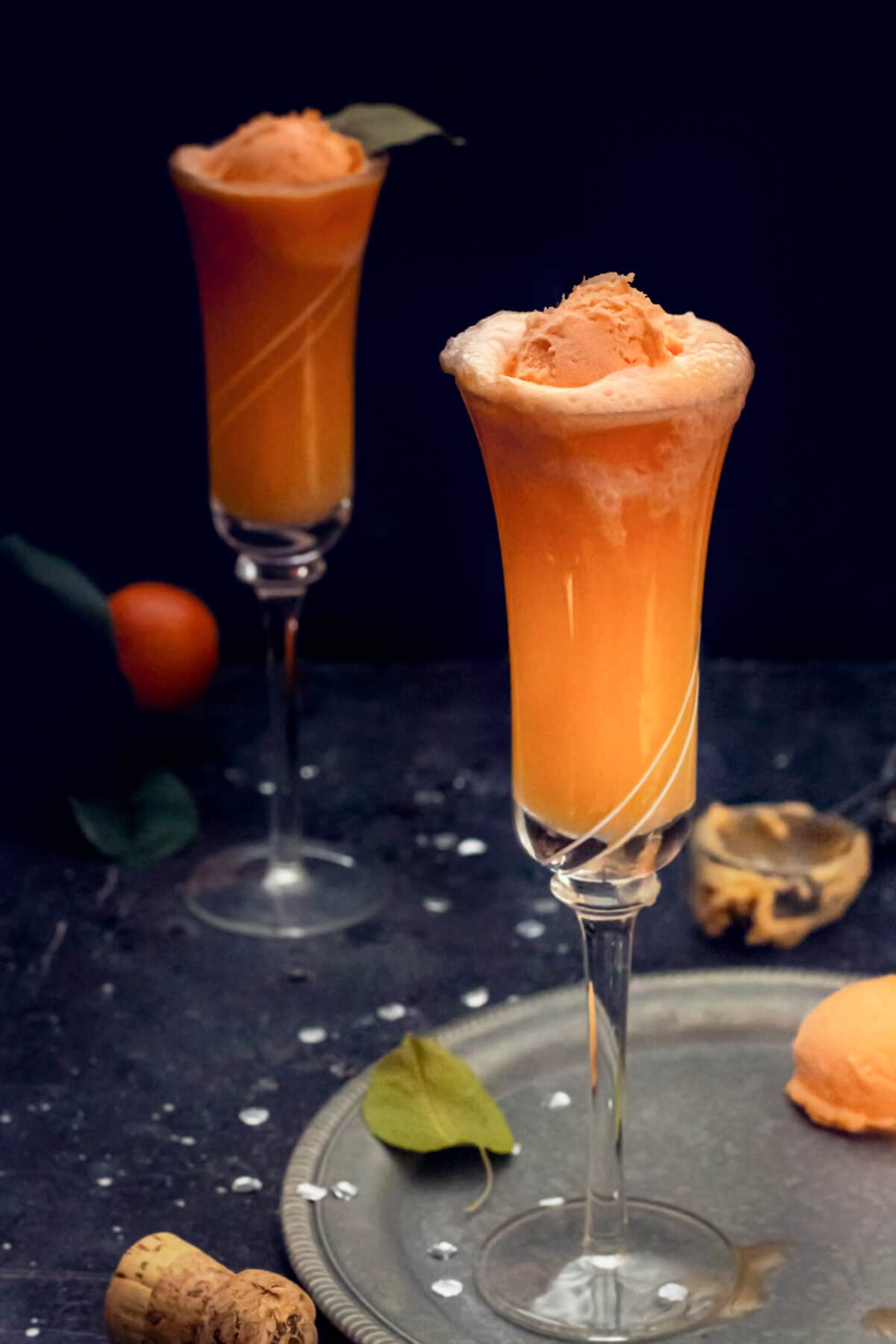 Two champagne glasses with orange sorbet mimosa drink.