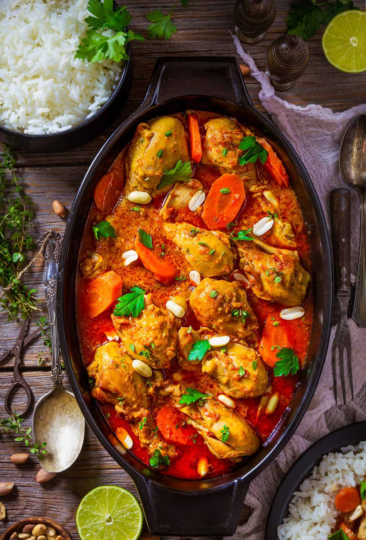 African peanut stew with chicken drumsticks in an oval dish on a table with white rice.